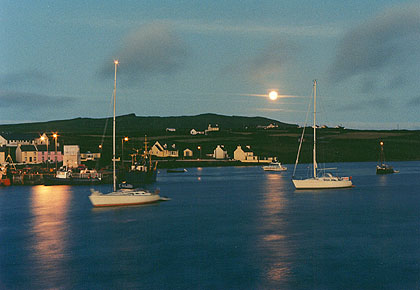 Moon setting at Portmagee Harbour, Kerry, Ireland.